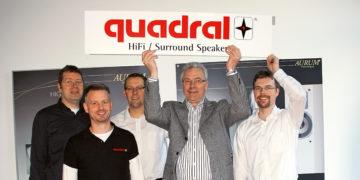 Einige Männer halten ein Schild mit dem Quadral-Logo in die Höhe.