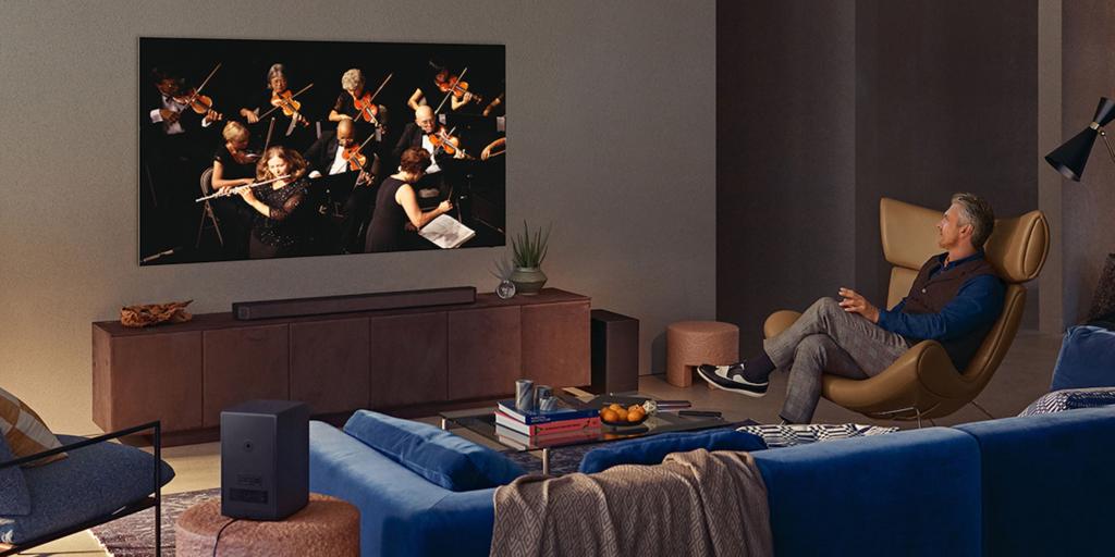 In einem stylisch eingerichteten Wohnzimmer sitzt ein Mann auf einem Sessel und schaut auf einen an der Wand befestigten Fernseher, der Orchestermusiker:innen zeigt.