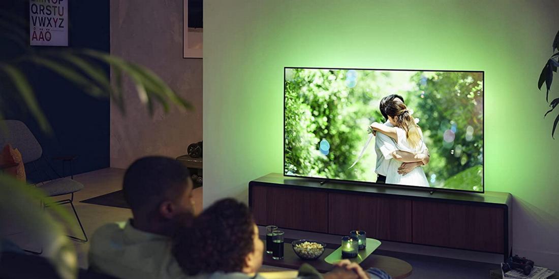 Pärchen schaut fern auf seinem Philips-Ambilight-Fernseher